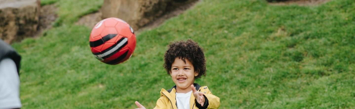 cheerful black boy playing with ball